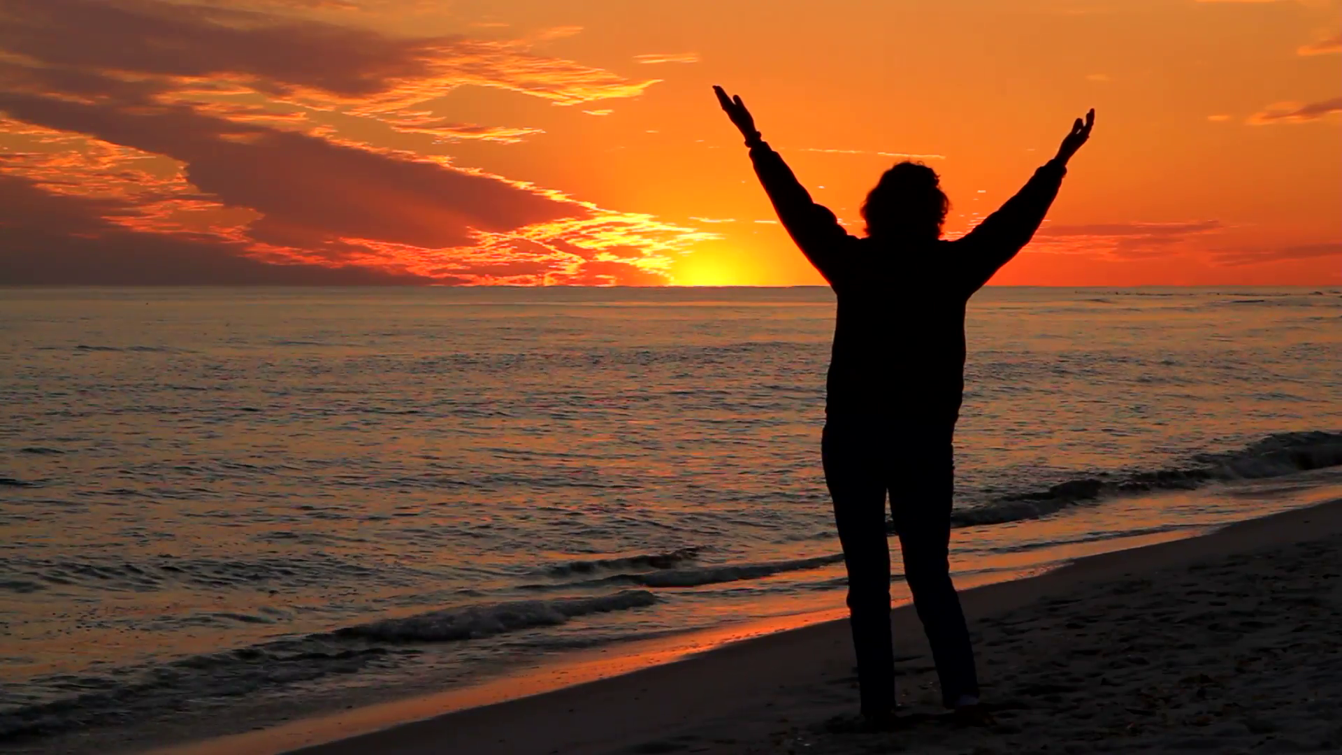 Image of a woman with hands raised at sunset in front of the ocean